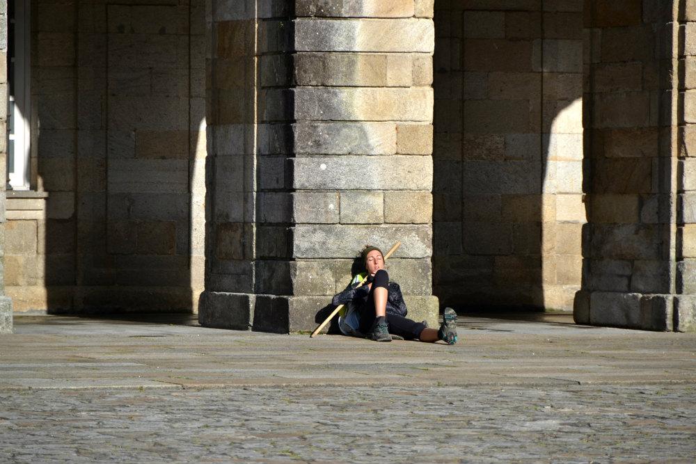 A pilgrim contemplates their journey on Praza do Obradoiro
