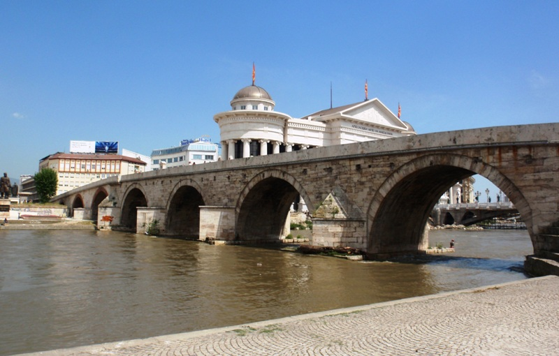 Old and New: Skopje's iconic Ottoman-era Stone Bridge over the River Vardar, with the Archeological Museum in background (Photo: Chris Deliso)
