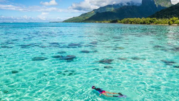 woman-snorkeling-in-crystal-clear-blue-water-of-tahiti